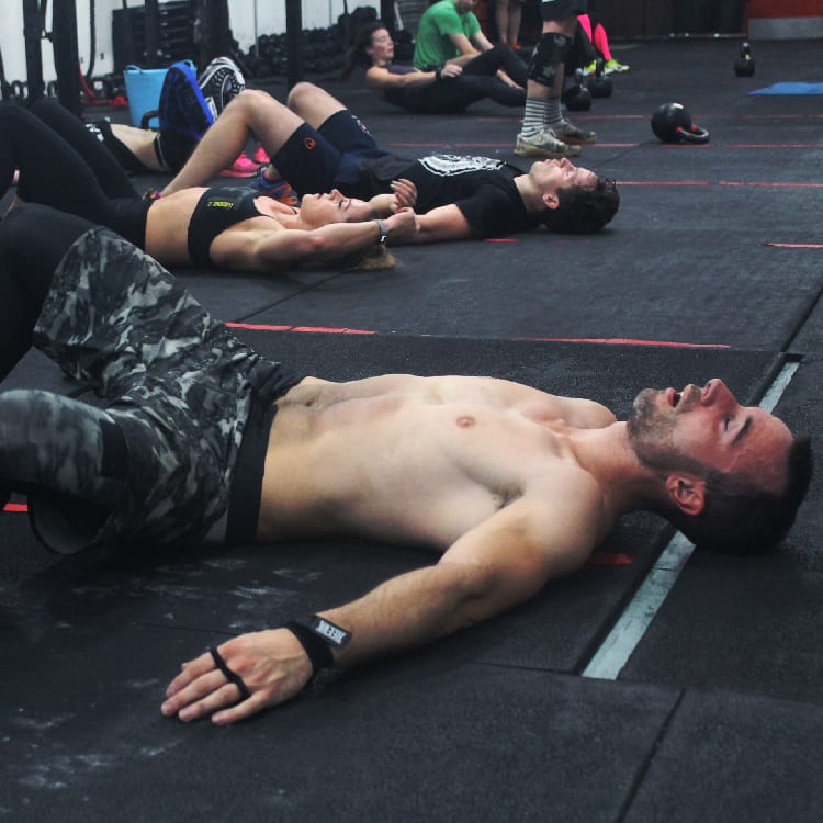 Male and female athletes exhausted on the floor after workout