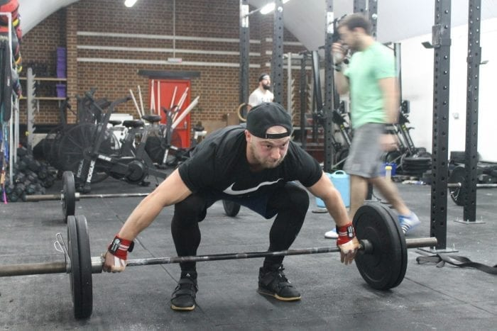 man standing over barbell
